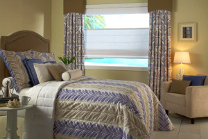 A beautiful bedspread and custom pillows on a bed next to a window with a top down bottom up white roman shade and stationary side panel draperies.
