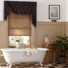 Black valance with gold pattern and trim over a light brown natural shade in a bathroom.