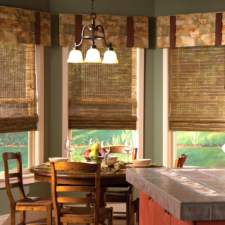 Three patterned mock roman valances with deep cherry brown banding over three natural shades in a light brown with no lining in a woodsy dining room.