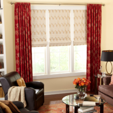 Beige flat roman shades with a gold pattern on them under red embroidered rod top draperies hanging on brushed nickel decorative hardware.