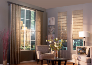 A modern living room with beige draperies on a big window next to two smaller windows with hobbled roman shades made in the same fabric as the draperies.