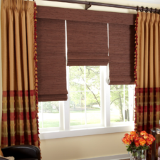 Three cherry wood colored natural roman shades on one fabric wrapped headrail under draperies that are half gold and half plaid on deep brown decorative hardware.