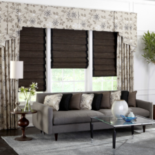 Three windows in a living room with deep brown natural shades under light beige patterned side panels and a cornice box with the same fabric as the draperies.