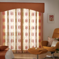Orange patterned sheers under an orange fabric wrapped cornice box in a bedroom with orange pops of color.