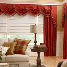 Red embroidered cornice with swags and cascades over draperies made out of the same fabric, all over white hobbled roman shades in a living room.