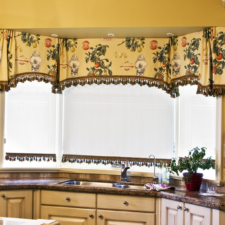 A patterned yellow fabric valance with brown and gold trim over white roman shades with the same brown and gold trim in a kitchen.