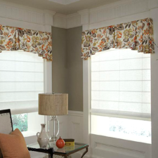 White roman shades under a patterned fabric valance.