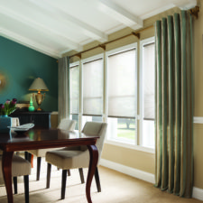 A dining room decorated in blue, brown, and beige accessories with four windows that each have a white roller shade on it under two panels of draperies that are blue, yellow, and brown striped being held by decorative gold hardware.