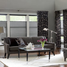A modern living room with top down bottom up cell shades in the windows and black, patterned draperies on each side of the windows.