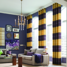 A living room with purple walls, grey couches, and decor in purple and gold with grommet top draperies in puple and yellow.