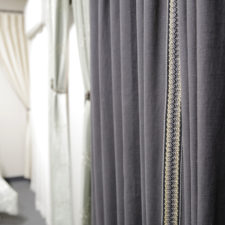 Blue linen draperies with a contrasting gold trim.