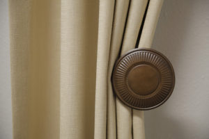 A closeup of a wood tieback holding beige linen draperies.