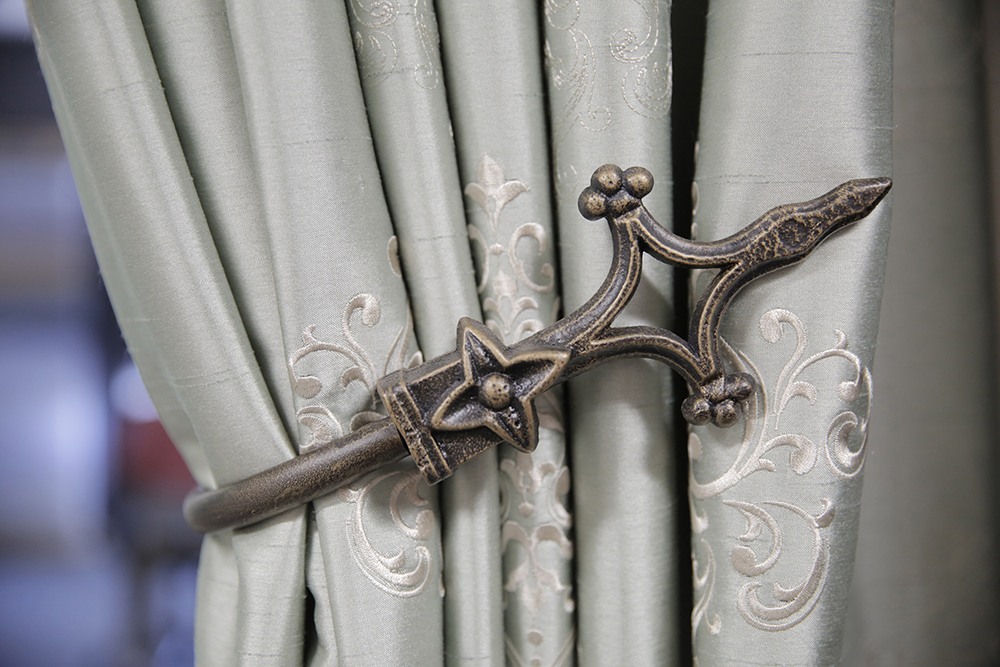 An intricate and elegant tie back adds the fine details in designer window fashions.