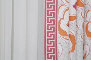 White, orange, and pink draperies patterned with flowers and a pink trim on the edge of them over solid white sheers.