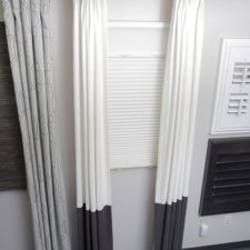 Gold hardware holding pinch pleated draperies that are a white material until the bottom third where they are a brown material all over a sun up sun down cellular shade