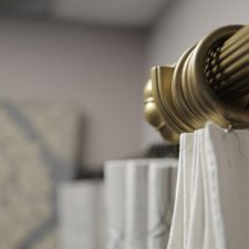 A close up of gold painted wood hardware holding off white solid draperies.