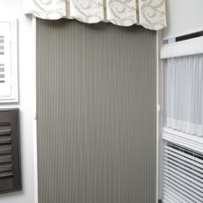 A large, grey slidevue shade with off-white rails under a patterned fabric valance in a showroom next to different types of shades and blinds.