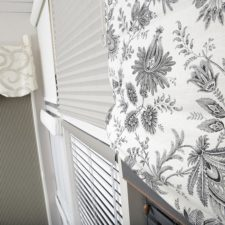 A close up of a patterned roman shade and in the background five other types of custom shades can be seen.