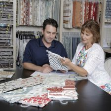 A young man and older woman sitting at a table that is covered in fabric samples in a room full of books of samples.