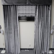 Draperies under an inverted pleat valance and over a roman shade, all made out of a grey velvet fabric and all concealing a TV.