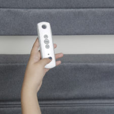 A woman's hand holding a small remote with three buttons on it in front of two shades.