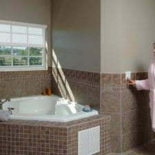 Woman standing in her robe in the bathroom smiling as she presses the button on the wall to have her automated window shades go down.