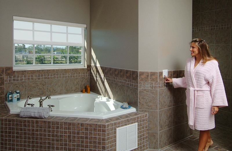 Woman standing in her robe in the bathroom smirking as she presses the button on the wall to have her automated window shades go down.
