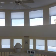 Roller shades on eleven windows on a high wall facing a lake.