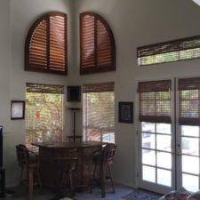 Corner of a living room with shutters covering quarter circle windows above four windows covered in woven wood window shades.