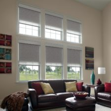 Two rows of three windows half covered by layered roller shades shining light into a living room with brown leather couches.