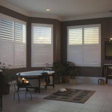 Three white faux wood shutters semi-open in a bathroom overlooking a bathroom lit my candle light.