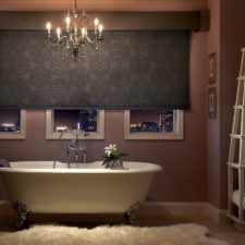 Black intricately designed large roller shade that is half open overlooking downtown from a bathtub.