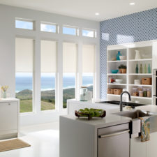Four thin white roller shades side by side on four vertically long windows overlooking the ocean in a kitchen.