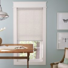 White textured roller shades over a window the is looked out of at an at home architects desk.