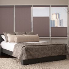 In a bedroom, four top down bottom up controlled roller shades with the two right shades covering the bottom half of their window.
