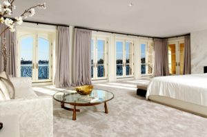 Custom curtains framed around french doors overlooking the ocean in a bedroom.