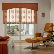 Transparent floral orange curtains half up on sliding glass door in the corner of the room with a lounge chair facing outside.