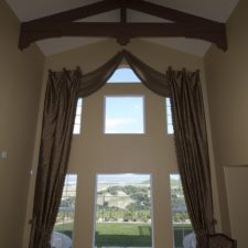 Long vertically hung drapery panels of elegant fabric framing two rows of three windows.