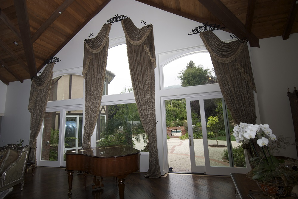 Three top treatment drapery swags elegantly hanging over three large windows in a high ceiling living room.