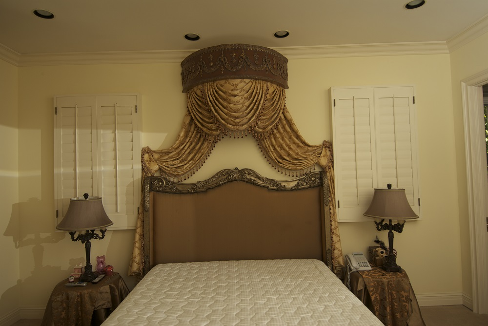 Gorgeously designed draperies hanging over the top of a bed from detailed wood cornice box.