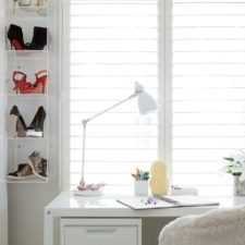 Wood vinyl shutters open to let natural light in on a modern at home desk.