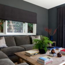 Brown colored roman shades in their open position with matching custom draperies in a comfortably designed living room.