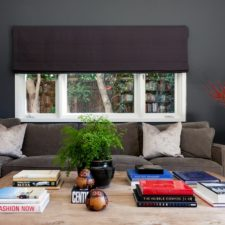 Custom roman shade made of dark fabric half open on a living room window.