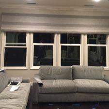 Grey roman shades in a modern designed living room in up position.