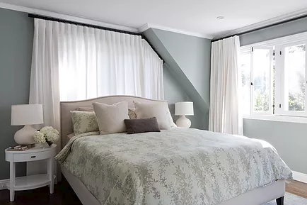 Grey and white bedroom with custom curtain hardware to accommodate angled ceiling drop next to window