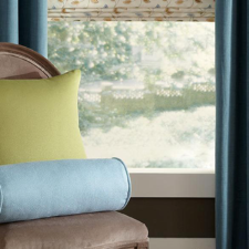A beige velvet upholstered chair with two throw pillows on it - one green and blue - in front of blue linen draperies on top of a floral patterned roman shade that has blue, green, and beige colors.