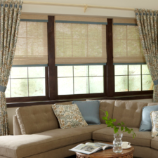 Three windows next to each other, each with a beige natural shade and light blue edge banding all under patterned draperies with the same color blue tiebacks.