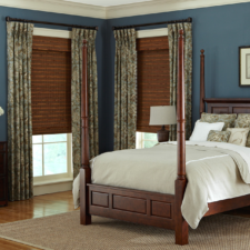 Brown woven wood shades under patterned draperies in a bedroom with pillows made in the same fabric as the draperies.
