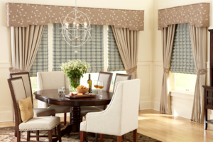 A dining room with blue striped hobbled roman shades under beige draperies with patterned tiebacks and fabric wrapped cornice boxes.