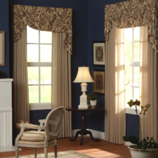 Patterned asymmetrical fabric valances over solid beige sheers.